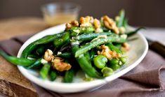 Ελαφριά και υγιεινή πράσινη σαλάτα που μπορεί να σταθεί επάξια δίπλα σε καλά κυρίως πιάτα. Τα καρύδια, ψημένα ή όχι, δίνουν τραγανή υφή και το ντρέσινγκ μια ζωντάνια.