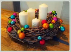 This rustic DIY Advent wreath with branches, colorful shiny balls and fat white candles looks incredible!