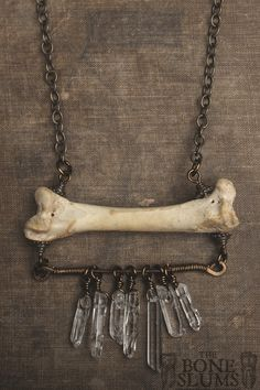 """This necklace features a single femur, with a piece of hammered brass wire beneath it that is wrapped in small gauge brass wire, and has several crystals dangling from it. This is a stunning necklace even though it is simple in design, but very unique.  It measures about 22 and 3/4"""" long, femur..."""