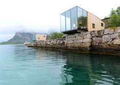 Glass and timber holiday cabins by by Norwegian architect Snorre Stinessen overhang the coastline of Norway's Manshausen Island.