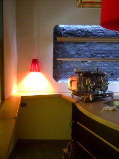 Dettaglio della continuità tra banco e mensole a vetrata. Lampadari su misura in seta rossa. Ristrutturazione in palazzo storico del 1600 per Gallery art bar.