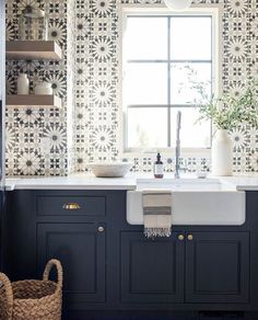 Moroccan tiles on kitchen wall with open shelving and navy cabinets