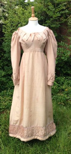 c1825 pink silk gown. Full skirt, slightly raised waistline at the front, natural waistline at the back. Gigot sleeves. Vandyked shape decoration around neckline, cuffs and ruched silk panel around hem. Hem padded with wool. Fastens at back with hooks, eyes and waist tie. Buttonhole in waistband. Pocket slit. I do wonder if the silk fabric is a wool-silk mix as it is quite substantial?