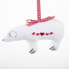 Polar bear decoration on white cotton with red embroidery and a red