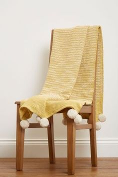Pom pom perfection! Shake up your living space with this yellow throw (but let's be honest, it's the pom poms we're loving!)