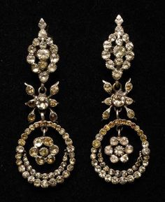 Earrings, 1775-1790, Spain. Silver and diamonds in three drops. First, diamond button, locking hinge, butt ring and ring. Second loop. Third: almond ring, inside which there is a rosette and crescent suspended. All with rhinestone clasps. (c) Museo del Traje