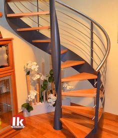Escalera de caracol con escalones de madera de roble y barandillas en acero inoxidable.