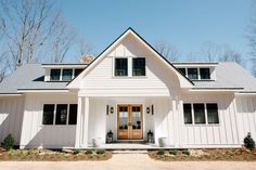Clean, modern farmhouse exterior with black windows, double doors, simple roofline. Green Mountain Construction in Charlottesville, Virginia