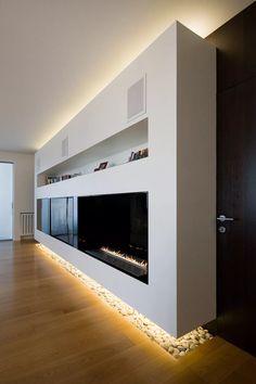 Idea soggiorno moderno con parete in cartongesso che ospita il camino a gas, tv e libreria. Bella l'idea della illuminazione sotto il muro e le pietre bianche