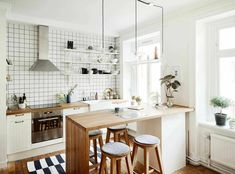 This cool contemporary small kitchen design has no upper cabinets, but it however makes up for it with an innovative three layered–shelve where white and black plates in a variety of shapes artfully rest