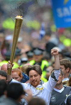 James McAvoy runs down Buchanan Street carrying the Olympic Torch in his hometown of Glasgow, Scotland on June 8, 2012