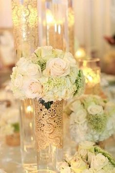 Beautiful elegant center pieces.Crystal vase with gold damask cut and white flowers.