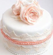 Romantic and delicate, the Roses and Frills cake combines textured fondant lace appliqués .Strings of edible candy pearls wrap the tiers with a feminine touch. This charming style is completed with hand-made gum paste flowers perched atop fondant lace.