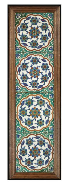 AN IMPRESSIVE IZNIK TILE PANEL, TURKEY, 1560-1575 made up of four tiles each decorated under the glaze in bright cobalt blue, tomato red and apple green with swirling flowerheads in a polylobed red-bordered roundel, the interstices filled with arabesques on a green ground