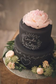 chalkboard wedding cake topped with pink peonies