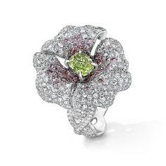 Lily Ring This lily ring is set in 18K White Gold with an oval Fancy Intense Yellow Green center diamond, Fancy Light Pink to Vivid Pink Diamond Melee' sweep up the petals while White Diamond melee' cascade over the petals