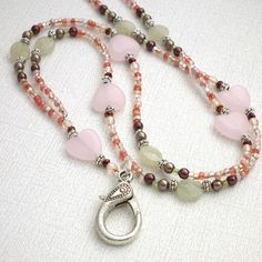 Beaded Lanyard - Pink Hearts, Soft Green Beads This beaded lanyard features soft pink heart beads accented with soft pink crystals and dark burgundy seed beads and pearls. These are complemented by so