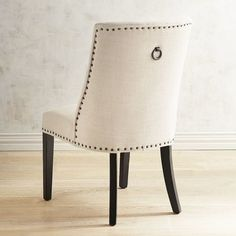 Corinne's larger seat and scoop back provide added support, deluxe style and comfort. With bronze nailhead trim, padded seat, solid wood legs and cotton muslin upholstery, this is a well-bred dining chair with superior genes.
