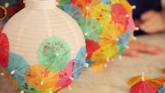 DIY Cocktail Umbrella Lanterns - Meg and Karen show how to use cocktail umbrellas to make party decorations. From the experts at HGT - Umbrella Centerpiece, Umbrella Decorations, Hawaiian Party Decorations, Cheap Party Decorations, Beach Party Decor, Caribbean Party Decorations, Aloha Party, Luau Theme Party, Tiki Party