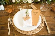 Place settings for the wedding dinner - wicker table mats, white linen and crockery, olive leaves to decorate the napkins and rustic style menus