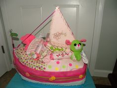 """(LEFT SIDE) I made this diaper boat for a baby shower. The expected baby girl's name is going to be """"Sailor"""". The diapers (2 different sizes) fill the hull of the boat with a hooded bath towel as the sail along with various baby items and toys. My first original design and completely handmade. Had a great time making it and it was a big hit!"""