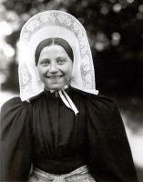 Streekdracht  Dirkje Vos in 1924  Vrouw in daagse muts, Huizen   Dirkje Vos uit Huizen was bijna 17 jaar toen ze in 1924 werd gefotografeerd. De daagse muts die ze draagt, de isabee, heeft in deze periode een hoge opstaande voorstrook.   Volwassen vrouwen droegen 's zondags de oorijzermuts. Die kreeg een vrouw rond haar 21e verjaardag samen met het zondagse pak en alle bijbehorende sieraden.