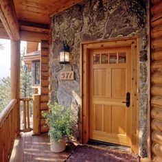 Log home with stone finish around the front door