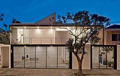 Claraboias e grandes portas com vidro deixam a luz solar entrar em diferentes momentos do dia nos ambientes deste sobrado de 210 m², em São Paulo. No projeto da Casa 14, a estrutura de concreto vazada integra o interior com o exterior.