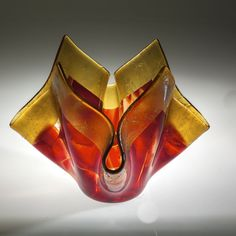 Flamenco Vase by Varda Avnisan. Fused glass vase. Made with iridescent amber glass and pieces of red and clear glass that are fused together. Great centerpiece for any space. Because of the handmade nature of the work each piece may be slightly different in color and size. Can be washed with warm soapy water.