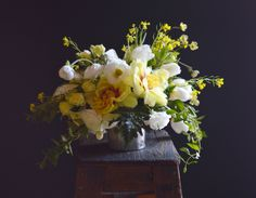 Mustard flowers, tree peonies, honeysuckle, ranunculus, roses and tulips in recycled tin can.