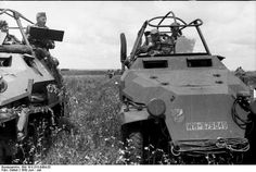 Two German SdKfz. 251/6 halftrack vehicles in the field, crews studying field maps, Russia, Jun 1942.