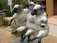 Three sheep doing a cancan - in front of a store - knitting in color