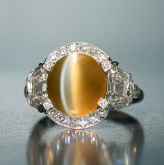 6.03 round cat's eye ring with 1.79 total of trapeze shaped, round and baguette diamonds set in platinum by Raymond Yard