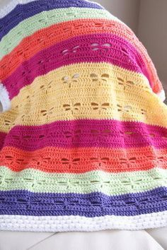 """This lovely blanket features a dragonfly design in colorful rainbow rows and a """"fluffy"""" white border. It makes a beautiful gift for a baby shower or a very pretty lapghan to keep you warm. This easy crochet baby blanket features bright and bold colors and a simple construction with an easy pattern repeat. Once you've got the hang of the stitch pattern, your hook will start flying! This is such a cute baby shower gift, especially for a springtime baby. Crochet HookH/8 or 5 mm hook Yarn…"""