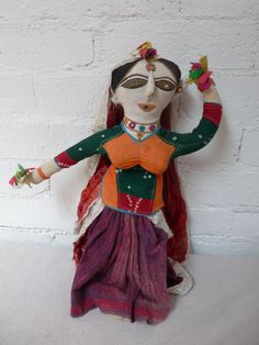 This doll, hand made with replicated, traditional Indian wear, is quite the babe! She wears her top snug, with her ample bosom, her nose piercing and black hair worn tightly in a bun. Her eyes are large and expressive, slightly larger than I've seen on other dolls, also there's mirror in place, giving her that additional sparkle that every female needs! She is flashy, no doubt about it! Measures 20 inches tall by 16 inches wide...