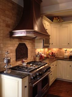 Love the hood, cabinets, and countertops. But the brick and the dark wood floors on a diagonal really makes the room.