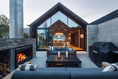 This sheltered outdoor living area at the Wanaka house features low sofas grouped around a large, wood-burning fireplace. The fully glazed gable ends on the main living pavilion allow a view through the house to the lake beyond. Outdoor Living Areas, Outdoor Spaces, Indoor Outdoor, Modern House Design, My Dream Home, Exterior Design, Building A House, Building Ideas, Beautiful Homes