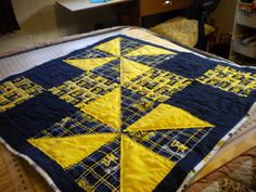 Three official University of Michigan cotton prints used in a large four square pattern including yellow pinwheels. Backing used is white Michigan print features blue and gold emblems. Hand quilted. Cotton batting. 39 x 39 square. Perfect gift for loyal fan, offering uniqueness and warmth. Could be wall hanging as well. Dont forget that baby of any U of M alumni.