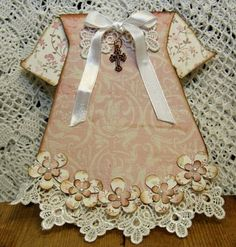 handmade card by Annelis scrap and Cardmaking Christening! ... card shaped as a baby's christening gown ,... ivory and natural colors ... real lace ... adorable layered punched flowers with tine pearls ,,. a cross too ... beautiful!