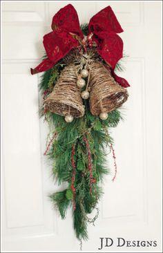 Grapevine glitter bell with velvet red ribbon on a cedar swag.