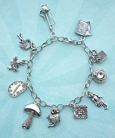 This charm bracelet features Alice in Wonderland inspired tibetan silver charms. Each charm is attached to a silver tone 7.5 inches chain bracelet with lobster clasp closure. SKU: 1002