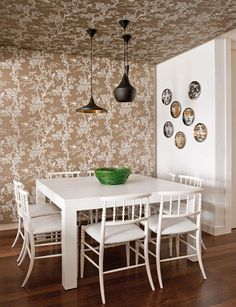 Like it how the wallpaper is run from wall to ceiling. Also love the Fornasetti plates on the wall.