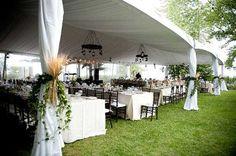 Rustic, homespun wedding tent, custom wagon wheel chandeliers, wedding tent decor.  Merrily Wed.