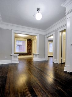 The best warm gray paint colour shown in Open layout with dark wood flooring and brick feature wall. Photo via Chris Nelson Inc floors grey walls The 4 Best Warm Gray Paint Colours: Sherwin Williams Style At Home, Brick Feature Wall, Brick Wall, White Baseboards, Warm Gray Paint, Neutral Paint, Baseboard Molding, Crown Moldings, Base Moulding