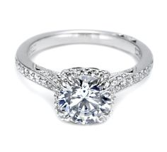 From Tacori's Dantela Collection, this unique setting creates a look that is a beautiful juxtaposition of modern, yet traditional. A stunning, diamond-surrounded round center stone is flanked by pave-set diamonds curving along the shoulders, with signature Tacori details along the sides for a woman with strength and sophistication. 603-749-3129