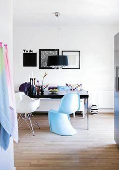 Spiseplassen består av en bordplate i komposittgranitt, en hvit Eames armchair, en blå Panton chair og en slagbenk som er kjøpt brukt. Stolene kan blant annet kjøpes fra Vitra. Bordplaten er slitesterk og trenger ikke vedlikehold, og varme kjeler kan plasseres rett på bordet. På veggen henger et tapet fra retrovilla.dk og et gavepapir i rammer fra Ikea. Den stripete vasen på gulvet er fra Kähler.