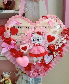 Vintage Keepsake Sweetheart Kitschy Kitty Valentine Posy Pocket.  Unique Original Design Handcrafted  Perfect To Hang and a Pocket ready to be filled with your own special Valentine Sweetness  This Handcrafted Posy Pocket Is Heart Shaped Made from Vintage Music Sheets.  Vintage Treasures throughout Bit and Bobs of Sweetness, Vintage Trims, Vintage Buttons and millinery flowers lace and more!  The Bottom Edge is Finished off with a Pink Crepe Ruffle Look Closely Im Sure Youll Discover More…