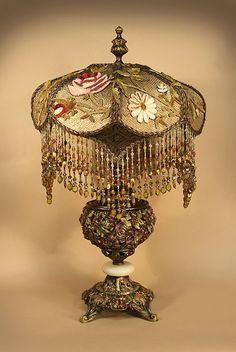 This beautiful, pierced metal, BRADLEY & HUBBARD, converted oil burning table lamp, encrusted with highly reticulated, painted floral details holds a 'CREAM PUFF' shaped shade. Pale gold silk lining is covered with gold metallic lace and then overlaid with embroidered flower appliqués. Four pointed corners are covered with antique gold lame and overlaid with old, gold bullion flourishes. Hand beaded fringe.