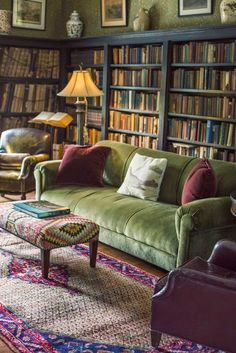 I love green and matching the walls to a solid low-armed couch makes the room look less busy. In rooms that are mostly bookshelves it's so hard to keep it from being busy.