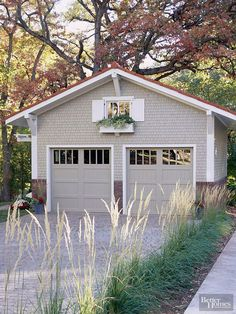 Extras, such as miniature shake shingles and a sweet window box, elevate the style of this detached garage. There's also a good aesthetic lesson here with the driveway and the brick garage detail: The two complement each other both in color and patterning.